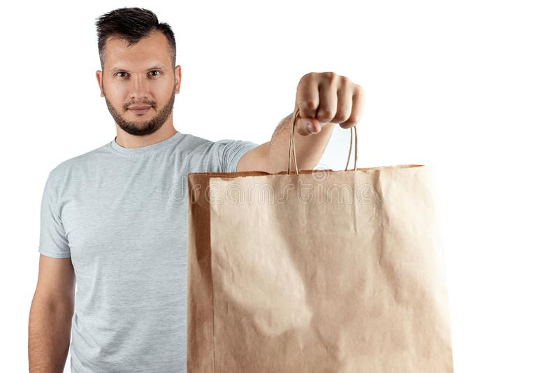 Man in a bright T-shirt giving a fast food order isolated on a white background. Male courier worker is holding food. Home. Delivery of goods from a store or royalty free stock images