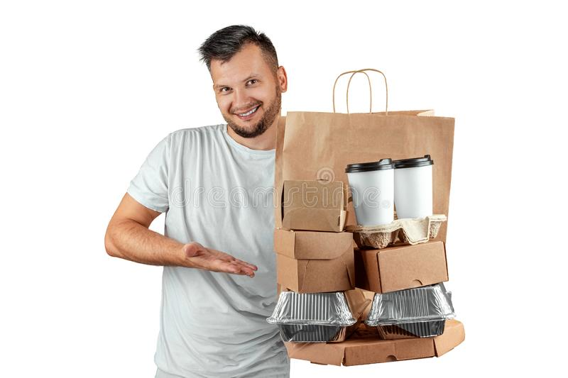 Man in a bright T-shirt giving a fast food order isolated on a white background. Male courier worker is holding food. Home. Delivery of goods from a store or stock photography