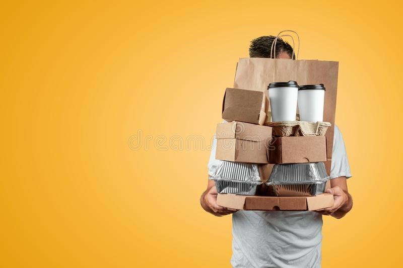 Man in a bright T-shirt giving a fast food order isolated on a yellow background. Male worker courier hold a packet of food. Home royalty free stock image