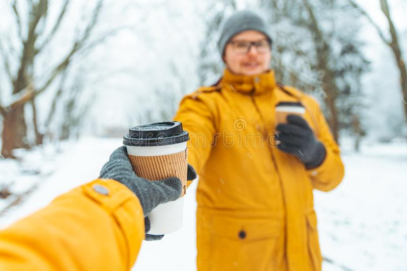 Man bring coffee to go for friends in snowed city park. Winter season royalty free stock photos