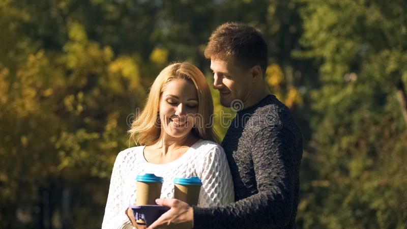 Man bringing coffee and snacks to woman who freezing outdoors, fast food meal royalty free stock images