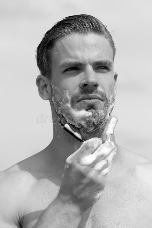 Man with bristle on clear sky background. Macho with concentrated face shaving chin with razor. Man with bristle on clear sky background. Macho shaving chin with stock photos