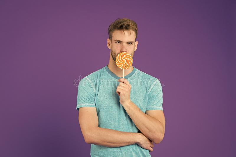 Man with bristle likes lollipop. Cheat meal concept. Sugar harmful for health. Guy hold lollipop candy violet background royalty free stock photography