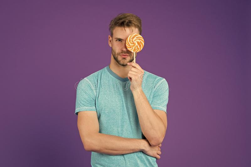 Man with bristle likes lollipop. Cheat meal concept. Sugar harmful for health. Guy hold lollipop candy violet background stock images