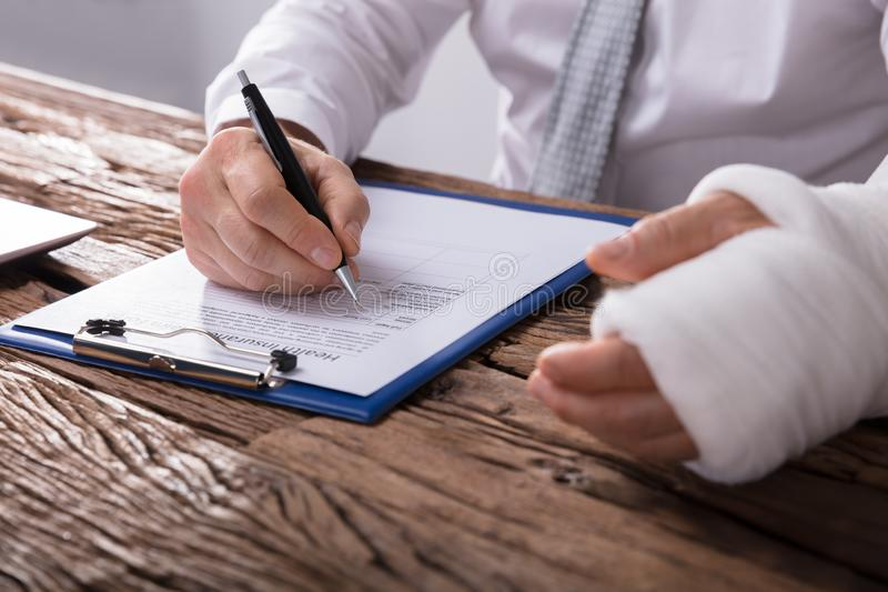 Man With Broken Arm Filling Health Insurance Claim Form. Close-up Of A Businessperson With Broken Arm Filling Health Insurance Claim Form On Wooden Desk royalty free stock image