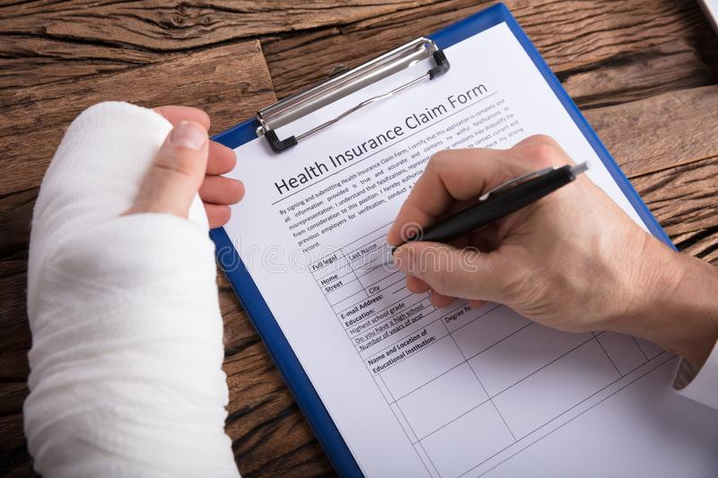 Man With Broken Arm Filling Health Insurance Claim Form. Close-up Of A Businessperson With Broken Arm Filling Health Insurance Claim Form On Wooden Desk stock photo