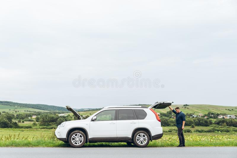 Man with broken car at road side royalty free stock photo