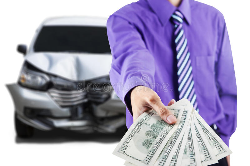 Man with broken car shows dollar money. Close up of businessman hand showing dollar money in front of a damaged car after collision stock photo