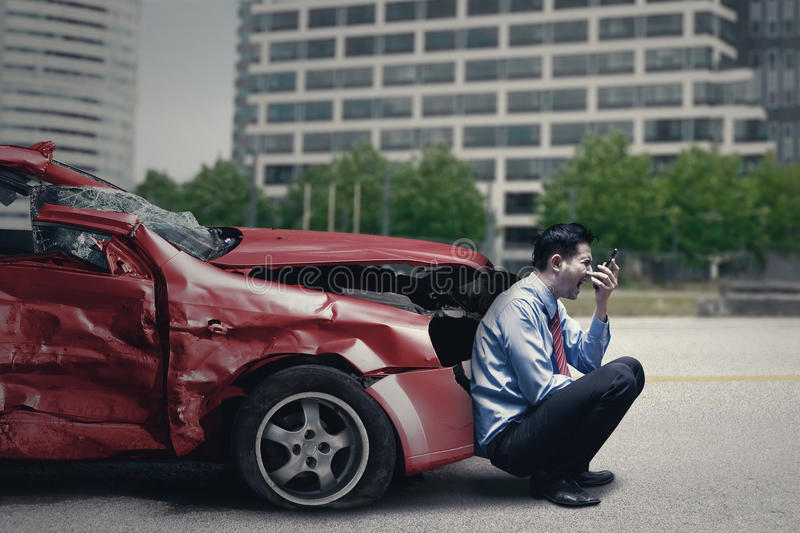 Man with broken car speaks on cellphone stock photos