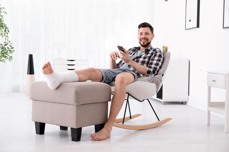 Man with broken leg in cast using mobile phone stock photo