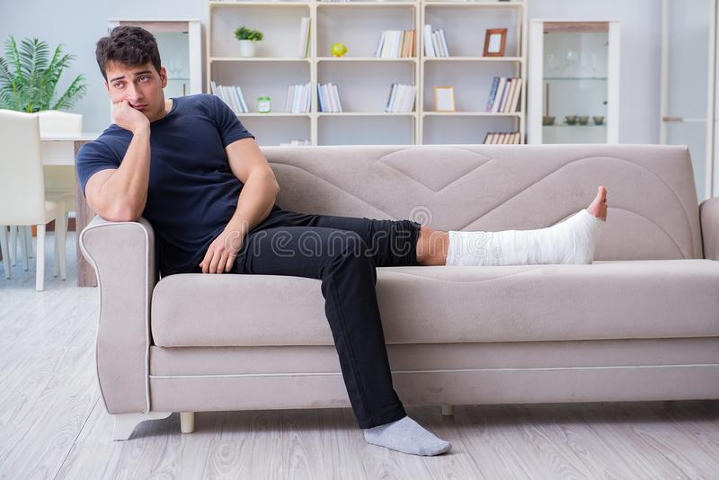 The man with broken leg recovering at home. Man with broken leg recovering at home stock photography