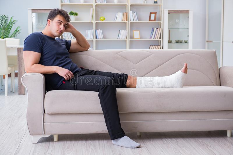The man with broken leg recovering at home. Man with broken leg recovering at home royalty free stock images