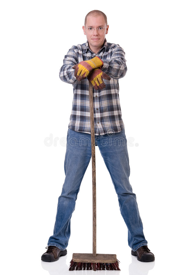 Man with broom. Full isolated studio picture from a young worker with a broom royalty free stock image