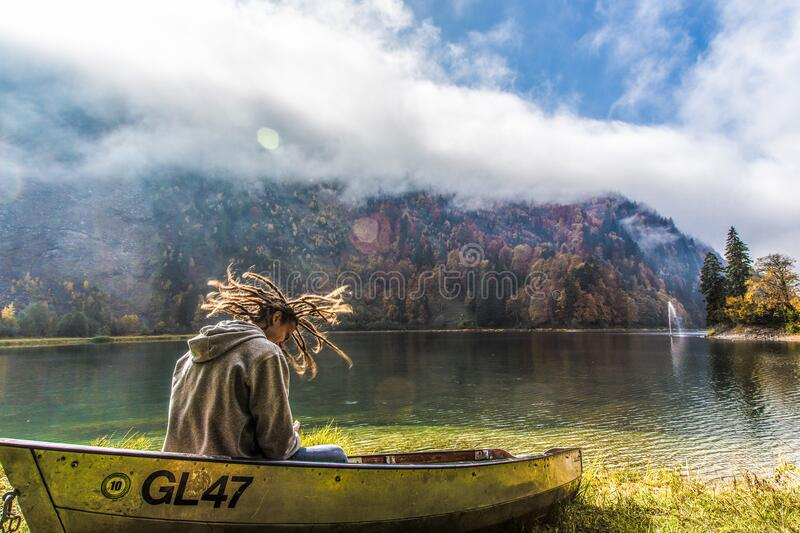 Man in Brown Hoodie Sitting on Yellow Paddle Boat Beside Lake Behind Hills during Daytime stock photo