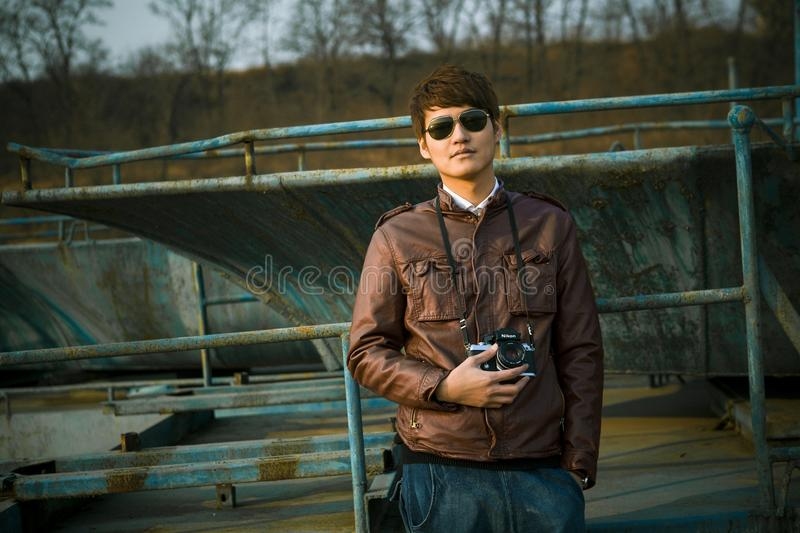 Man in Brown Leather Jacket Wearing Black Framed Sunglasses Holding Black Dslr Camera Standing in Front of Black Steel Bar during royalty free stock image