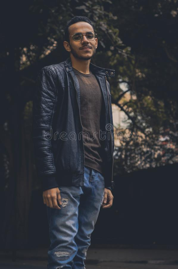 Man in Brown Shirt and Black Leather Zip-up Jacket and Blue Denim Pants royalty free stock photography