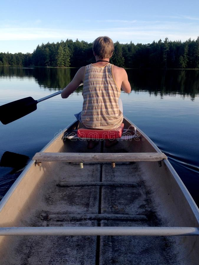 Man In Brown Tank Top On Boat Holding Paddle On Calm Water With Green Tall Trees During Daytime Free Public Domain Cc0 Image