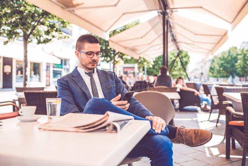 Man browsing internet on smartphone sitting at outdoor cafe. Young man browsing internet on smartphone sitting at outdoor cafe royalty free stock photos