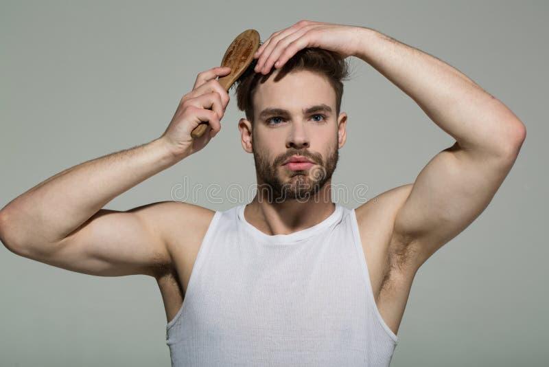 Man brush hair with hairbrush on grey background stock photo
