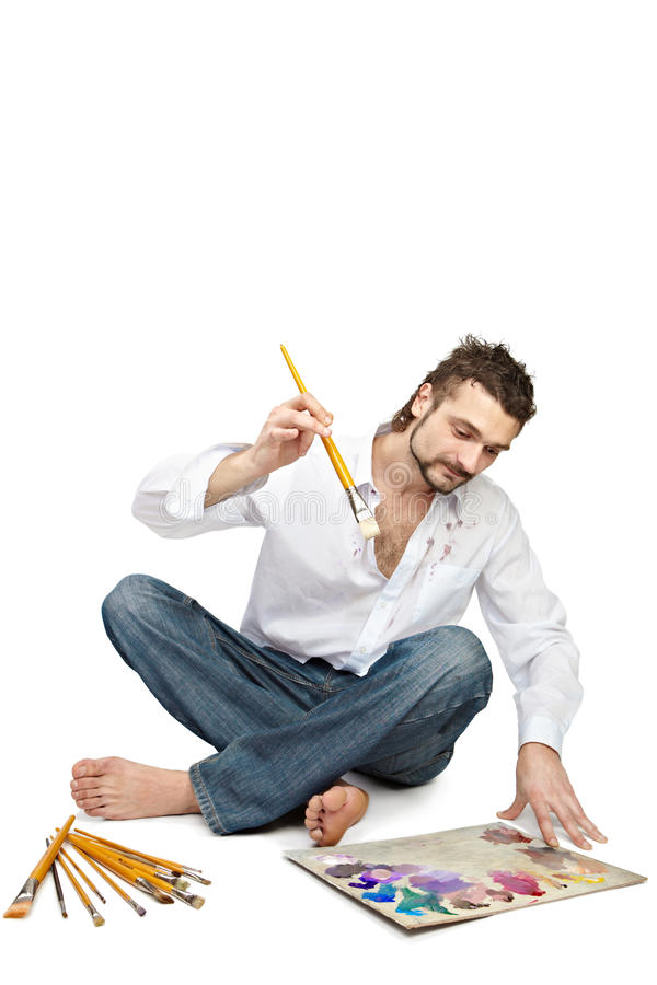 Man with brushes sitting near palette stock photography