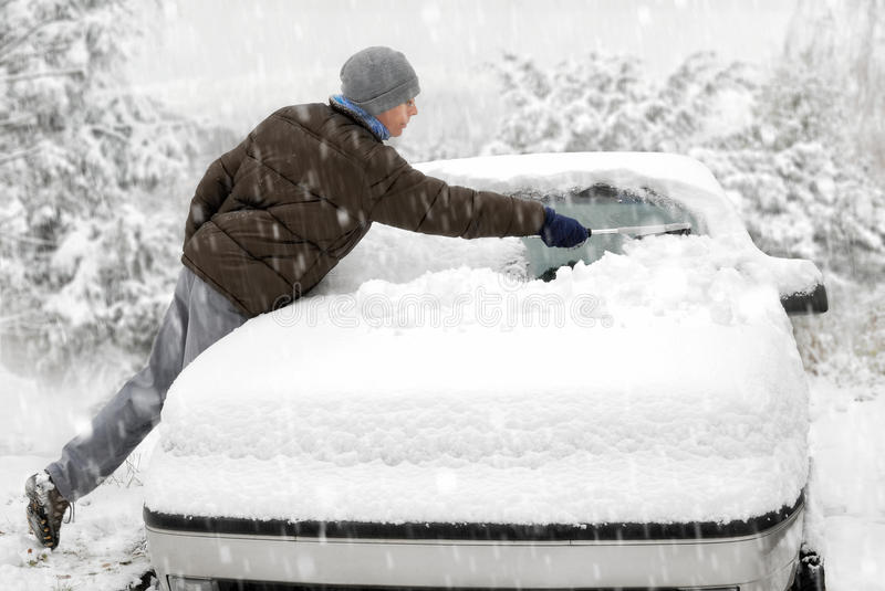 Man brushes snow off his car stock image