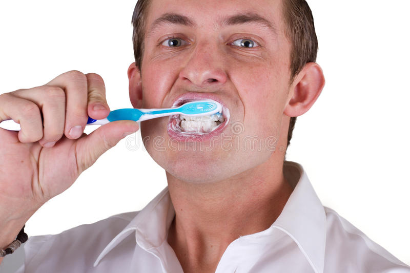 Man brushing his teeth. Adult male brushing his teeth isolated on a white background, closeup picture stock photography