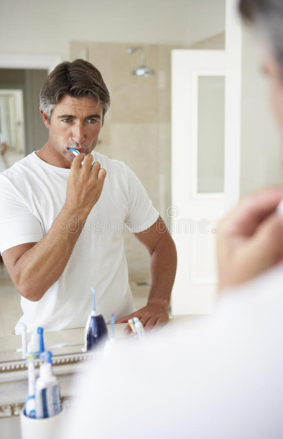 Man Brushing Teeth In Bathroom Mirror stock photo