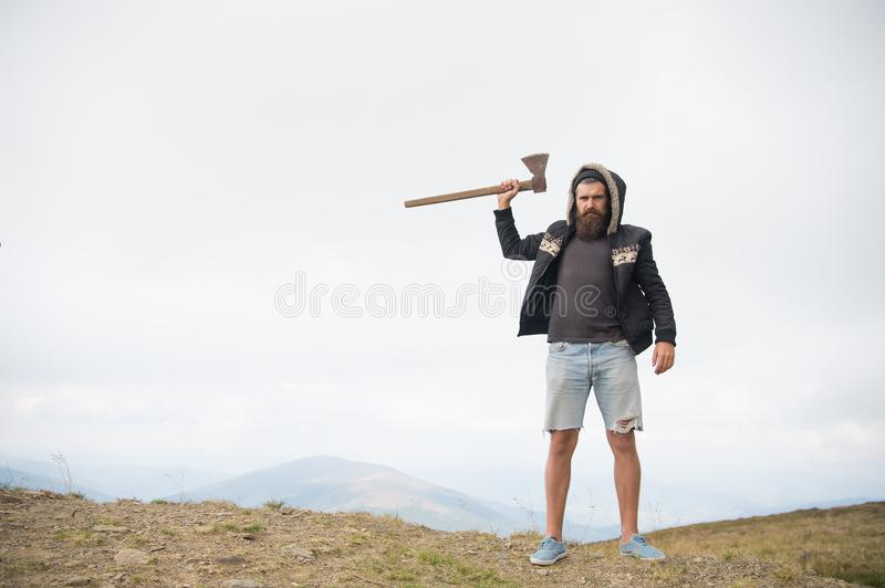 Man brutal bearded hipster with axe stand on mountain top royalty free stock photography