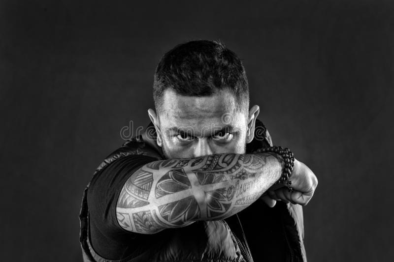 Man brutal guy cover face with tattooed arm. Tattooed elbow hide male face dark background. Visual culture concept. Tattoo can function as sign of commitment royalty free stock photography