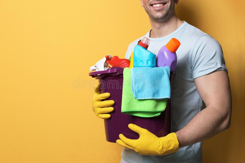 Man with bucket of detergents on color background stock photos