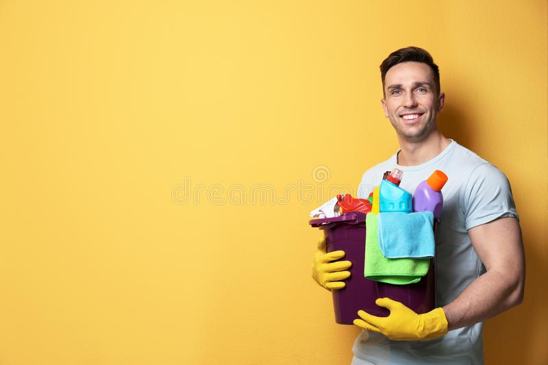 Man with bucket of detergents. Space for text royalty free stock photo