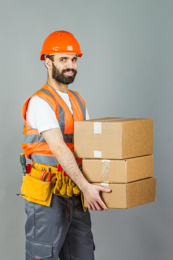 A man-builder in an orange helmet with a cardboard box in his hands. On a gray background stock photo