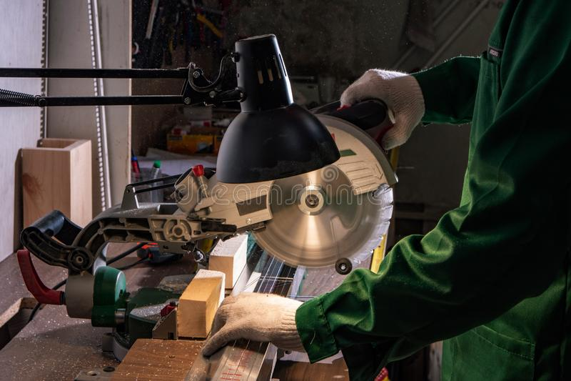 A man builder saws a board with a circular saw in the workshop. A man builder saws a board with a circular saw in the factory workshop stock photography