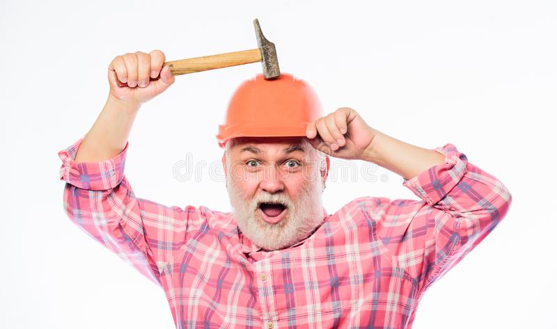 Man builder use hammer tool. mature bearded man in hardhat. construction build. professional repairman in helmet stock image