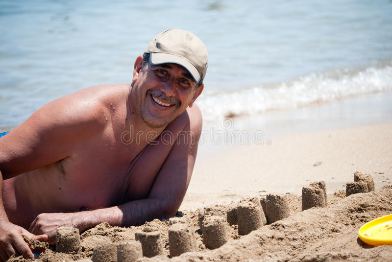 Man building castles on the sand royalty free stock photo