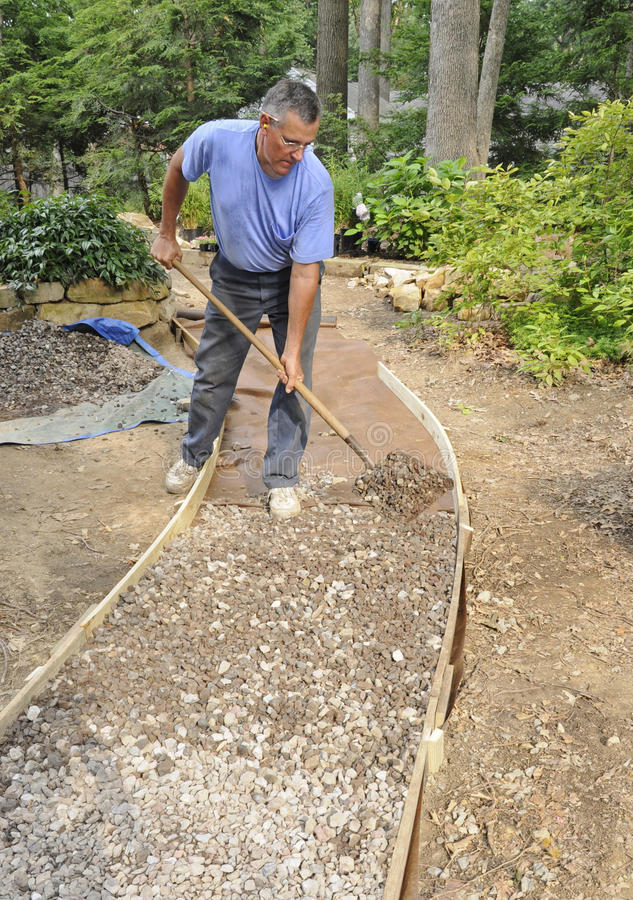 Man building gravel path royalty free stock photos