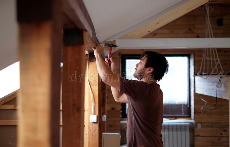 Man building a house and workimg with hammer and wood.  stock photos