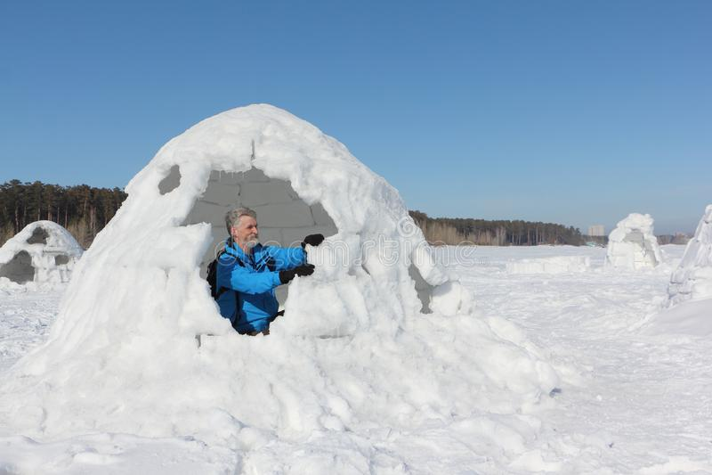 Man building an igloo on a snowy reservoir in winter royalty free stock photos