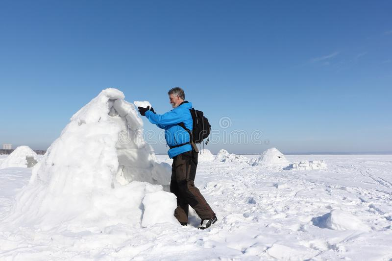 Man building an igloo in winter. Man building an igloo on a snowy reservoir in winter, Novosibirsk, Russia stock photos