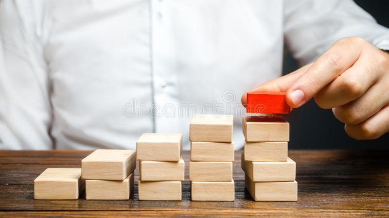 A man is building a ladder or growth chart from blocks. Strategy planning business expansion. Climbing the career ladder. Increase. In income, organization of royalty free stock photography