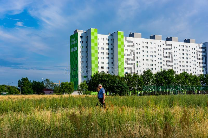 Man and building. Poznan, Poland - July 10, 2018: Man and woman walking between a field with plants on a sunny summer day in the Orla Bialego district. High stock image