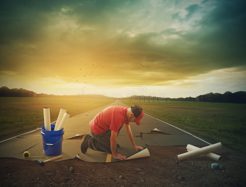 Man building a road. Surreal image of a man building a road with his own hands stock photography