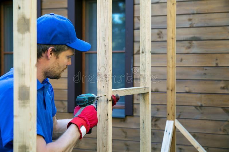 Man is building a shed in backyard. Man in blue hat and shirt is building a shed in backyard royalty free stock photo