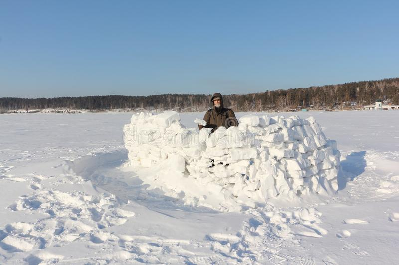 Man building a snow wall, Siberia, Russia stock image
