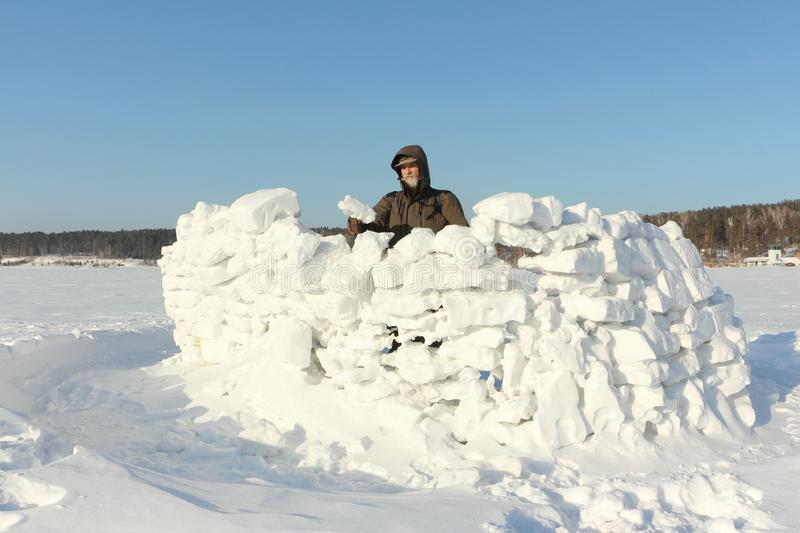 Man building a snow wall, Siberia, Russia stock photo