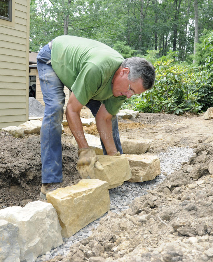 Man building stone wall royalty free stock photography