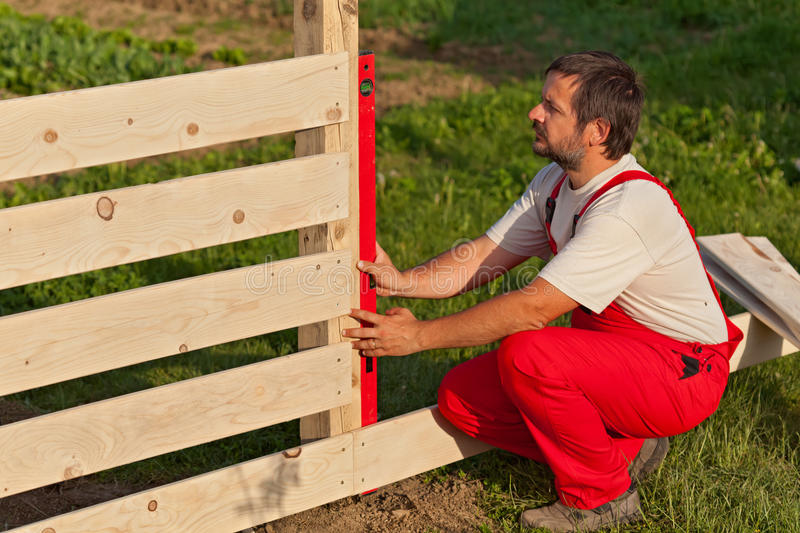 Man building wooden fence royalty free stock photography