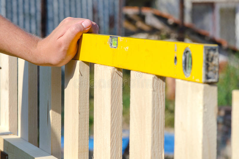 Man building a wooden fence and checking with spirit level. Close up of his hand and the tool in a DIY concept. royalty free stock images