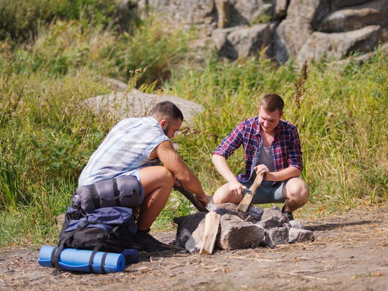 Man Builds Fire Pit Around Open Camp Fire. A men scribbles a tree to set fire to a fire. Summer vacations in the open air stock photos