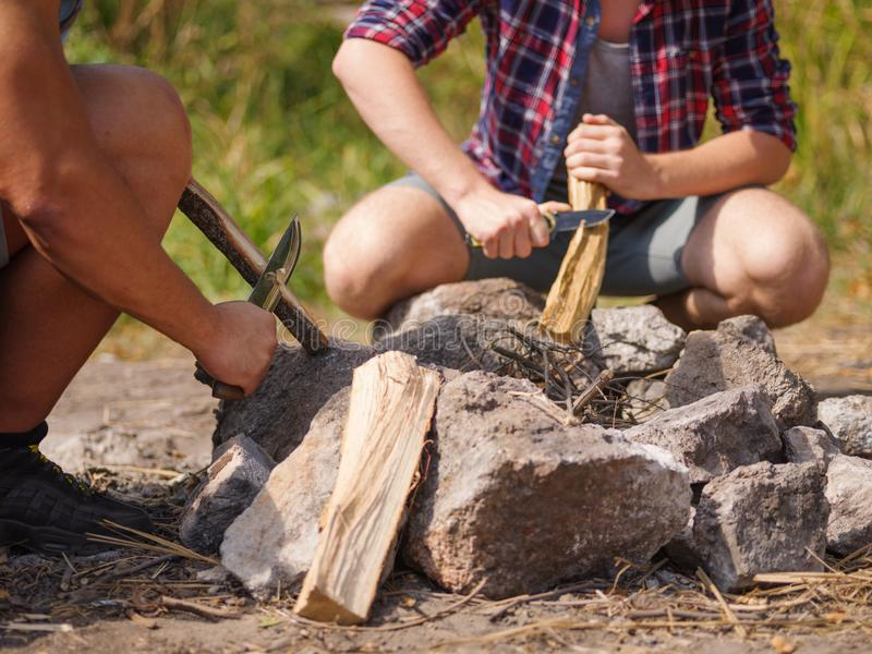 Man Builds Fire Pit Around Open Camp Fire. A man scribbles a tree to set fire to a fire. Summer vacations in the open air stock image